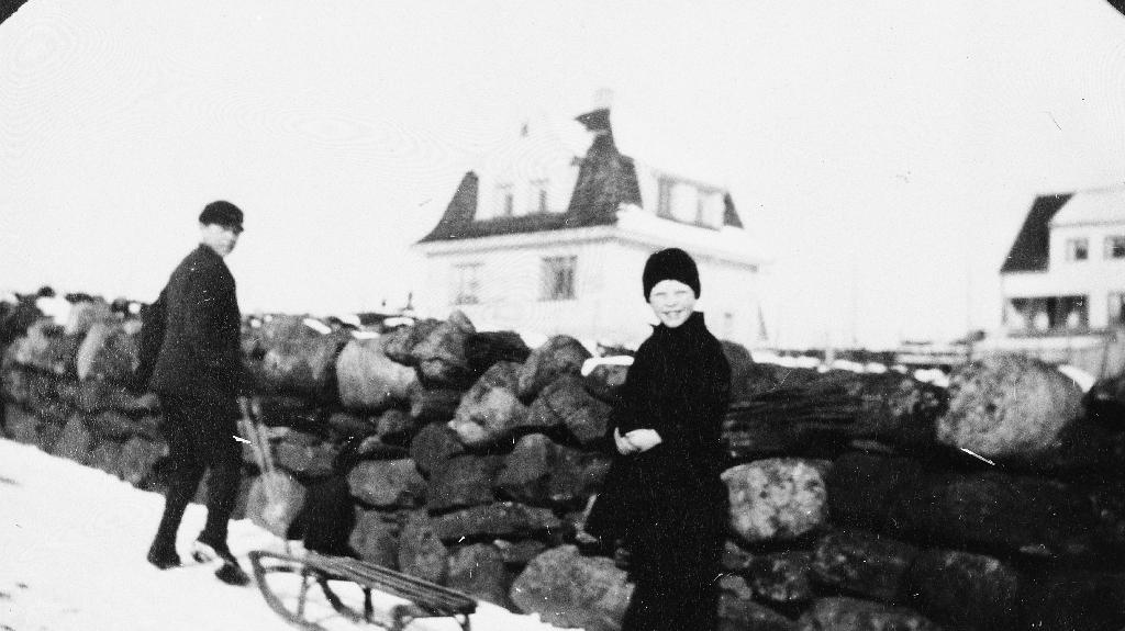 Sledetur i Henrik Carlsen bakken på Brynehaugen. Til høgre Åsa Braut, broren dreg sleden. Huset til lærar Torstein Lye i bakgrunnen.
