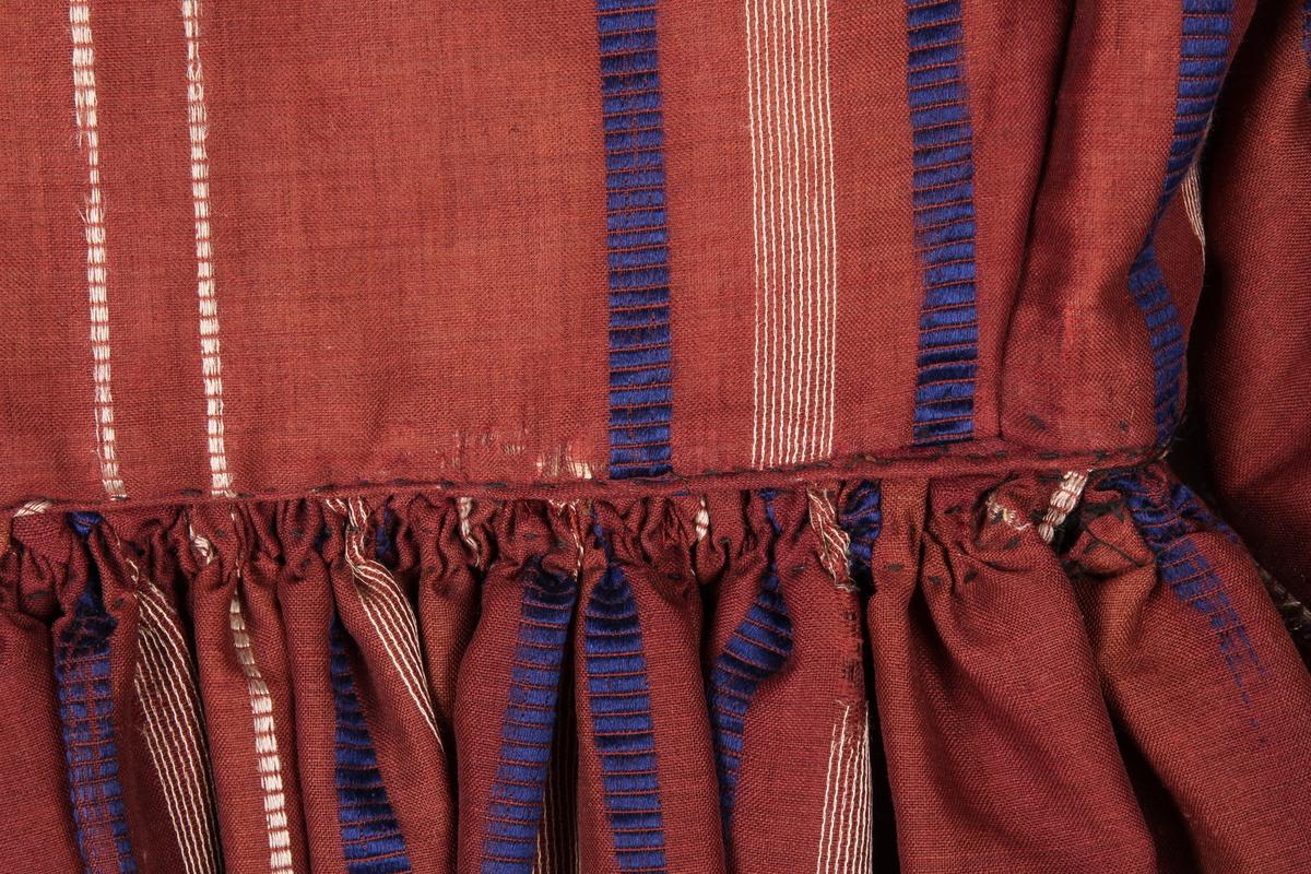 Rødfiolet silkekjole. Livet er skrådd inn mot midjen og har en isydd spile på hver side foran, samt to midt bak. Livet har en stolpe midt foran med 6 knapper, halsen er smal og har påsatt en tyllkant med hvite glassperler og tre smale silkebånd. Kjolen har lange ermer, som fra albuen og ned er påsydd en kappe i samme farge som kjolen ellers, med grønne frynsekanter. Skjørtet er sterkt rynket og festet til livet. Skjørtestoffet er skjøtet ca 2/3 ned på stoffet. Nederst på skjørtet er det satt på en forsterkningskant /skonning / skonnering av sateng. Stoffet er noe falmet slik at det ser ut som om den er brun. I stoffet er det innvevde vannrette striper av blått og brunt, loddrette striper av gult. Disse stripene er visse steder slitt bort, mens stoffet under er like fint. De fleste sømmene er håndsydde, mens noen av sømmene i livet er sydd med maskin. Det er spor etter at kjolen har vært sydd inn i livet tidligere.
