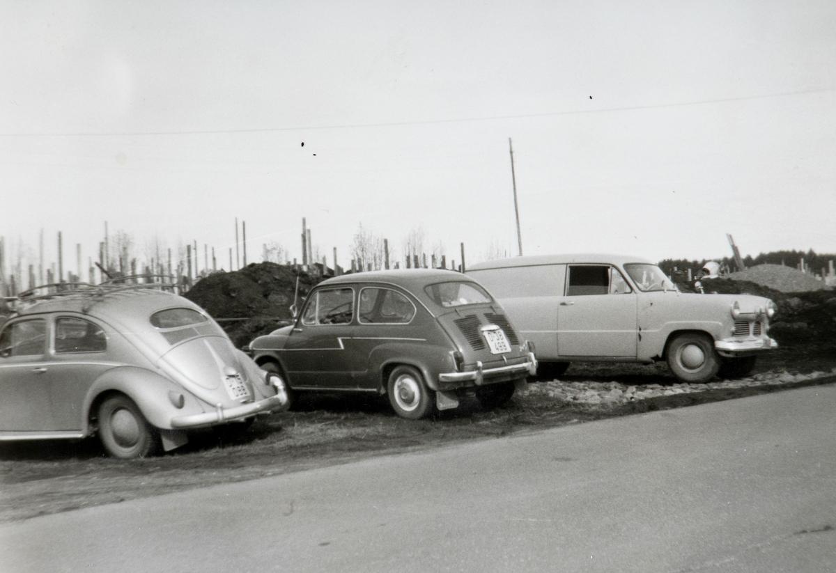 Kvello, Stange. Selvbygging, husbygging, dugnad, parkerte biler.  Fra venstre: Folkevogn (oval bakrute tilsier årsmodell 1953-57), NSU Jagst (kromstripen langs siden viser at det er den tyskproduserte versjonen av Fiat 600), Ford Taunus 12M varebil 1953-ca. 1960.