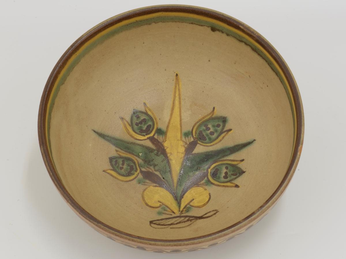 Stilisert blomsteroppsats i bunnen av bollen. Brunt, gult, grønt. Striper i samme farger på innsiden av kanten. Utvendig bord i samme farger.