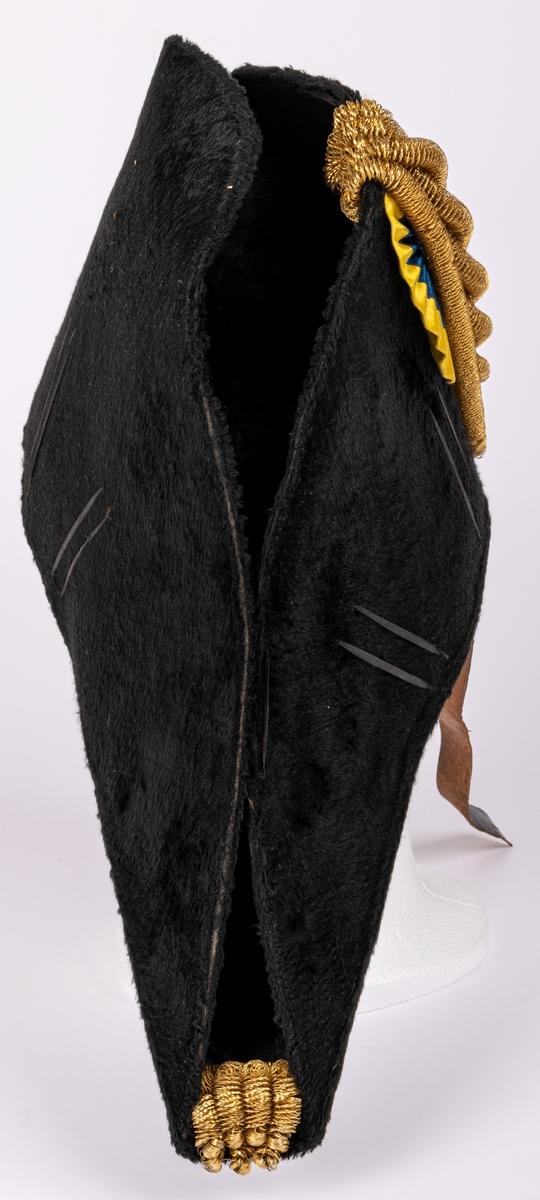 Uniformshatt till civiluniform. Hatten, svart av båtform, med rel. hög kulle och uppvikt sidobräm, stor blågul kokard jämte gyllene spiralband och mässingknapp med grip och riksäpple.  Längd 47c,m, bredd 15cm, höjd 21cm. Träfodral till hatt för civiluniform. Fodralet hopsatt i sinkningsteknik tillstympat trekantig form av björkträ. Längd 56cm, bredd 20cm, höjd 27cm.  I fodralet ligger tidningar från 1844.