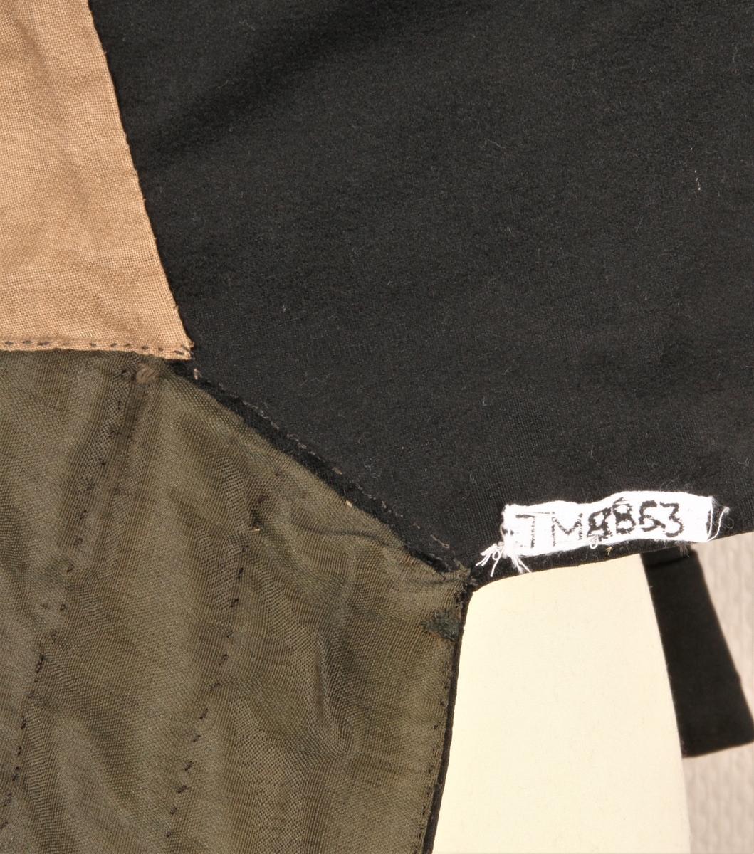 """Livkjole i svart, blankt ullstoff. Fóret i jakka er i toskaftvevet lin, og fóret i """"skjørtene"""" er er et svart/ grønt tynt toskaftvevet ullstoff. Ei stor hempe er pådsydd bak i kragen. Det er knapphull på begge slagene. Hele livkjolen er håndsydd, i hovedsak med brun lintråd."""