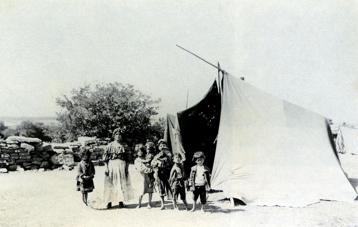 En romsk familj utanför sitt tält i Vickleby på Ölands västra sida. Tältet är av en äldre typ, så kallat tretoppstält, som användes i Sverige under tidigt 1900-tal. Det finns ingen ytterligare dokumenterad kunskap om personerna på bilden, hur länge de bott på platsen eller när bilden är tagen. Boendestandarden bland svenska romer var under 1900-talets första hälft mycket varierande. Familjer som hade det bättre ställt kunde äga flera tält, medan fattigare familjer enbart hade ett tält. Man sov då där marken var minst lerig. Under 1940-talet förbättrades levnadsstandarden och flera svensk-romska familjer specialbeställde nu bostadsvagnar. Att inte behöva sova på marken utgjorde en avsevärd förbättring av livskvaliteten. Eftersom vagnarna specialbeställdes kunde beställaren vara med och påverka vagnens utformning. Ofta fanns sovgemaket längst in, varpå vardagsrummet följde och köket låg längst ut. Denna utformning kunde dock skilja sig åt mellan olika vagnar. Generellt var dock vagnarna dåligt isolerade och kalla att bo i. Först på 1960-talet tilläts svenska romer att bli bofasta.
