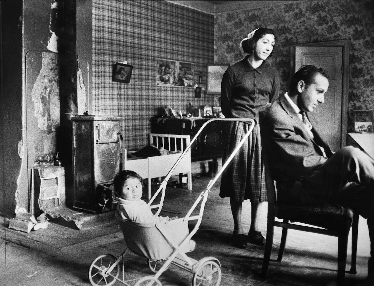 """Bilden föreställer en familj i sitt hem i Älvsjö år 1963. Bildtexten lyder: """"Sture och Rut bor fortfarande kvar med sina tre barn i rucklet i Älvsjö, där de bott sen 1954 i ett enda rum med en kamin som enda värmekälla och kokmöjlighet. De är moderna, trevliga ungdomar som hoppas på att få en småstuga med en verkstadslokal. Han är en duktig bilmekaniker men har hittills bara haft gårdsplanen att arbeta på."""" År 1885 stiftades en lag i Sverige som gjorde det olagligt att vara arbetslös, egendomslös eller kringvandrande. Samtidigt började kommunerna under 1900-talets första årtionden att utfärda vistelseförbud, lägerslagningsförbud och näringsförbud för romer och resande. Trots detta saknade de flesta svenska romer fast bostad fram till 1960-talet. Efter att de svenska romerna i Sverige erkändes som medborgare år 1952 uppstod debatt kring gruppens svåra levnadsförhållanden. En statlig utredning genomfördes under 1954-1956 där en av slutsatserna blev att fast bostad var nyckeln till att lyckas med skolgång och arbetsliv. Från och med mars 1960 hade möjlighet att rekvirera statsbidrag för kostnader i samband med romers bosättning, vilket förenklade möjligheten för svenska romer att få tillgång till permantenta bostäder samt i förlängningen studier och arbete. Processen kom dock att ta tid och många romer fick bo i slitna bostäder eller rivningshotade hus. Tre år efter att statsbidraget infördes bor denna familj fortfarande med mycket låg standard."""