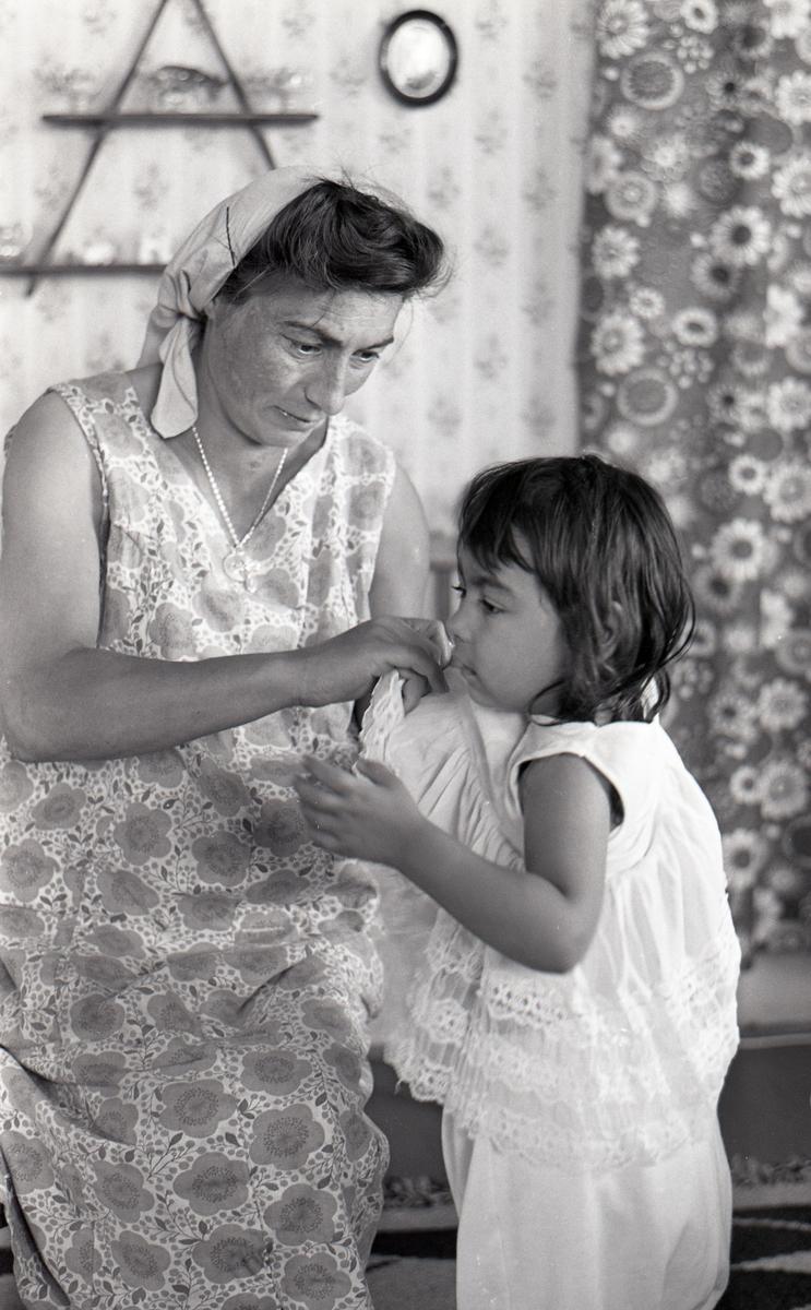 En mamma och hennes dotter porträtterade i samband med ett nyhetsreportage för Skånska Dagbladet sommare år 1963. I reportaget porträtteras familjen och hur de trivs med att ha blivit bofasta. fter att de svenska romerna i Sverige erkändes som medborgare år 1952 uppstod debatt kring gruppens svåra levnadsförhållanden. En statlig utredning genomfördes under 1954-1956 där en av slutsatserna blev att fast bostad var nyckeln till att lyckas med skolgång och arbetsliv. Från och med mars 1960 hade kommuner möjlighet att rekvirera statsbidrag för kostnader i samband med romers bosättning, vilket förenklade möjligheten för svenska romer att få tillgång till permanenta bostäder samt i förlängningen studier och arbete. Denna process kom dock att bli utdragen under flera år. Frågor om svenska romers förhållanden uppmärksammades mycket i media, långt i på sextiotalet.