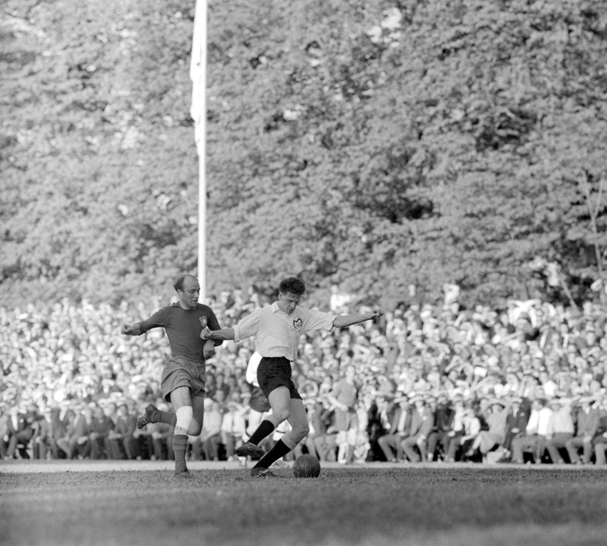 MAIFs centerhalv Lennart Hemming täcker boll för Gunnar Gren, en av svensk fotbolls allra största. Bilden är från Motala AIFs bragdartade avancemang till den svenska fotbollsallsvenskan 1957. Klubben hade visserligen vunnit Östra Götalands-serien men i kvalet stod storklubben Örgryte IS för ett respekterat hinder mot finrummet. I kvalets första kamp på Ullevi hade Motala vunnit en knapp seger och nu stundade avgörandet på Idrottsparken inför 12 863 åskådare. Efter en trevande första halvlek tog Motalalaget över handlingen mot en resultatmässigt komfortabel seger med 4-0 efter mål av Sören Nilsson på nick, två mål av Sten-Arne Lorin och ett distinkt skott från Gösta Löfgren. Allsvenskan var nådd.