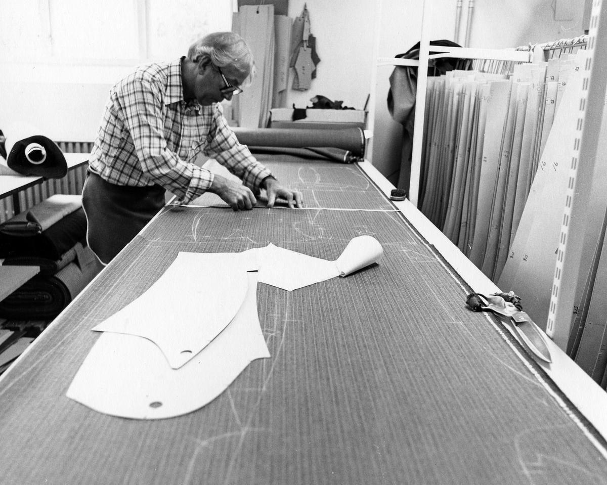 """Tillskärare Bjarne Eriksson ritar upp mönster på tyg att sedan klippas eller skäras till. Drabant AB, tillskärningen """"Skäret"""", bottenvåningen."""