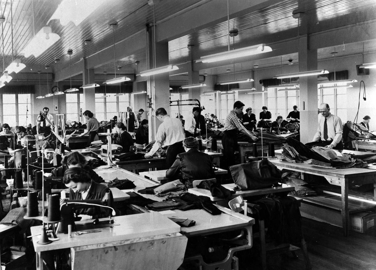 Drabant AB. En grupp män och kvinnor jobbar med tillverkning av byxor och kavajer.