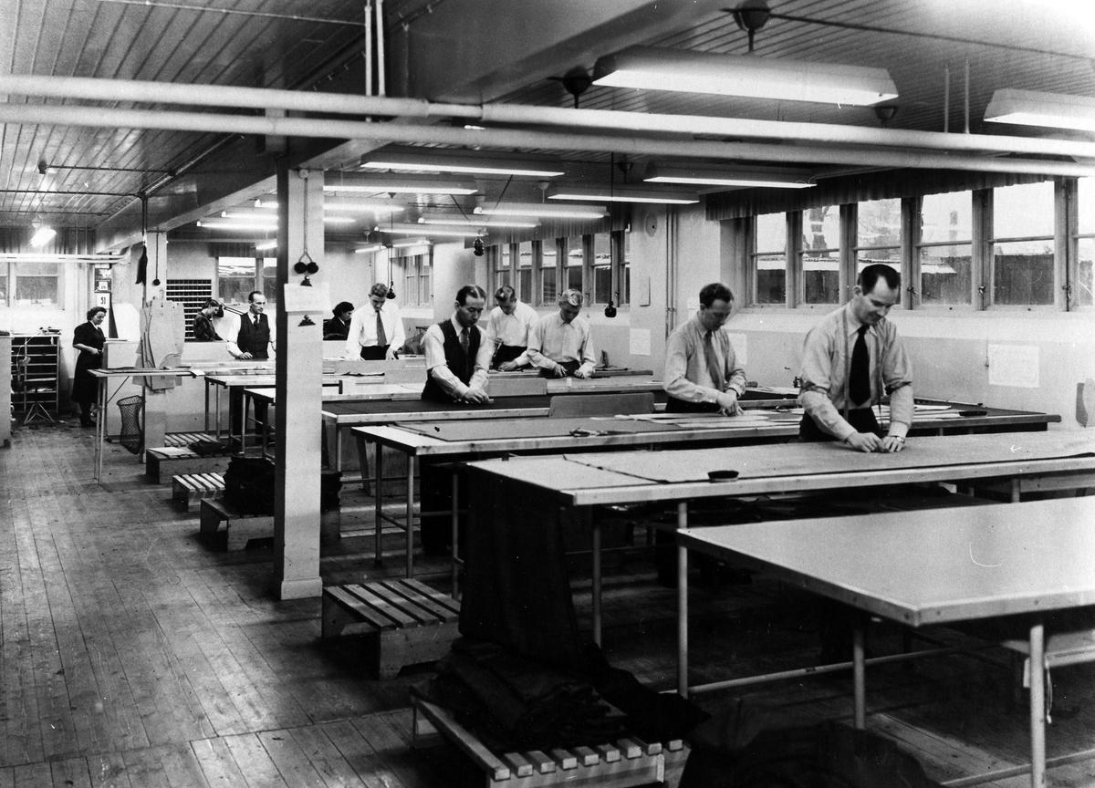 En grupp män och kvinnor arbetar med tillskärning av tyg till gjorda beställningar. Tillskärningen på Drabant AB:s bottenvåning.