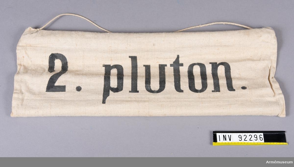 Skylt av tyg med träpinnar i sydda kanaler på långsidorna. Upphängningssnöre. Svart text: 2. Pluton.