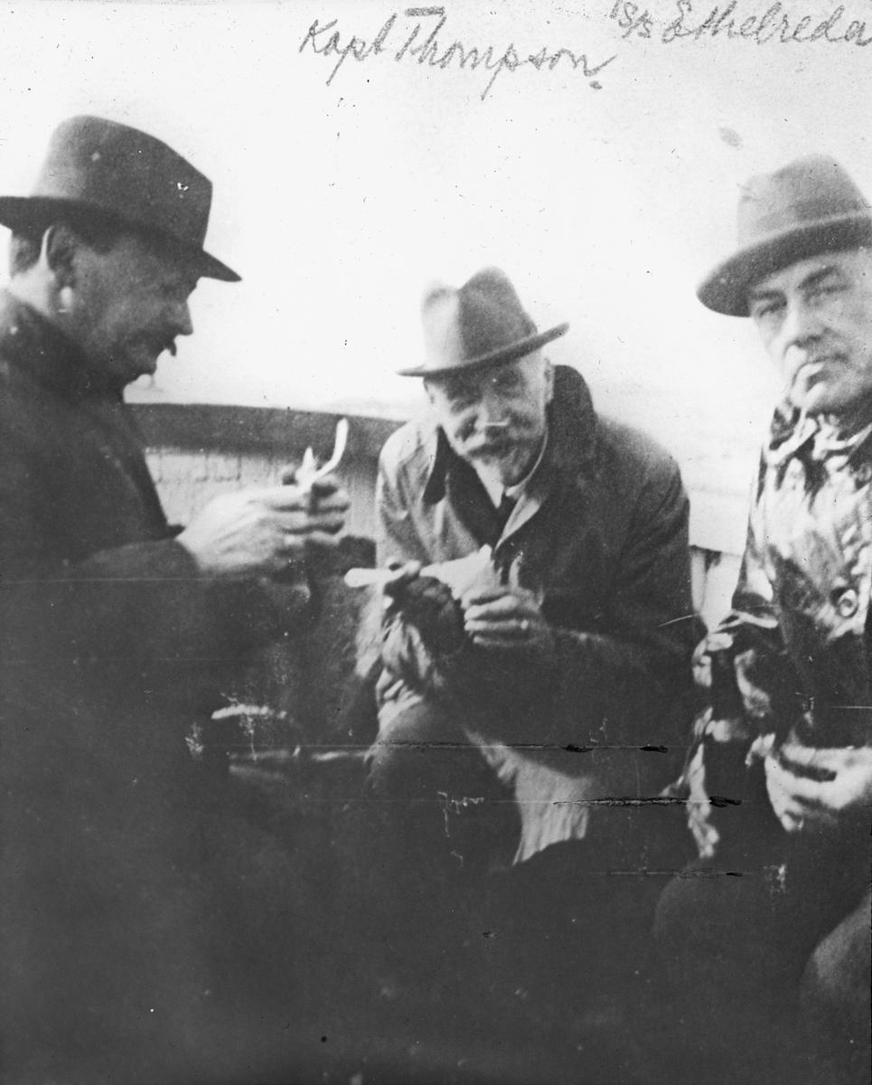 Nærbilde av tre menn i frakk og hatt ombord på et fartøy. De spiser mat. Merket Kapt. Thompson og S/S ETHELREDA.