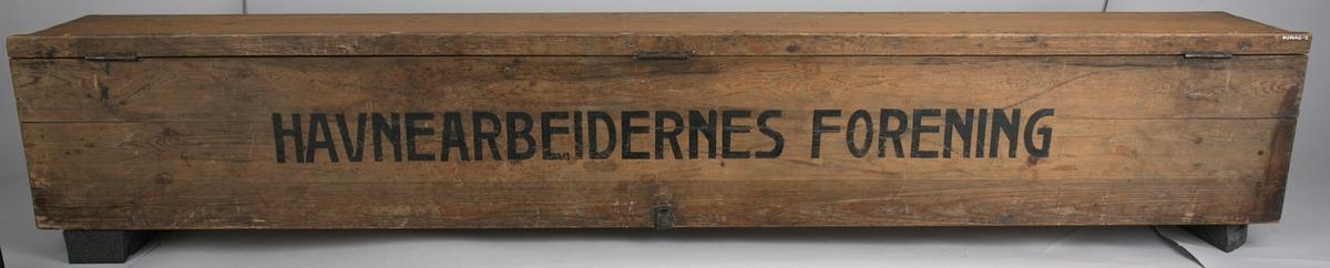 Fanekasse fra Bergen Losse- og Lastearbeiderforening. Rektangulær trekasse med hengslet lokk med låsbeslag. Kassen har jernhåndtak på begge kortsidene for bruk under transport.