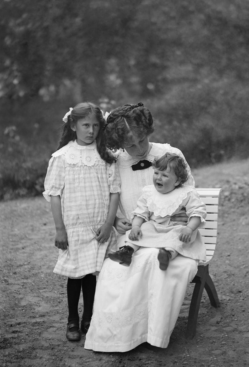 Ellen Signhild Spens, född Enhörning, har samlat barnen Anna och Christer för ett vackert porträtt. Ellen var dotter till konsul Gustaf Fredrik August Enhörning och Ellen Gerda Schubert. 1904 gifte hon sig med greve Gabriel Spens, godsägare till Engelholm i Sankt Anna socken.