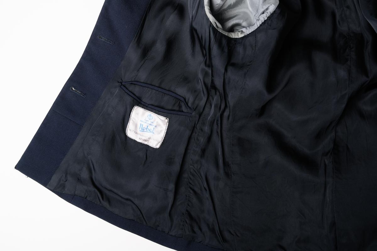"""Kavaj av terylene, mörkblå färg, för kvinnlig soldat i Frälsningsarmén. Kavajen är figursydd, enkelknäppt med tre plastknappar och försedd med slag. På axlarna sitter klaffar av blått tyg (ullfilt) med svart bandkantning samt knäppning med plastknapp. På vänster och höger rockslag är ett metallmärke """"F"""" fastsytt på en liten sexkantig, blå tygbit (labell), som i sin tur är fastsydd på rockslaget. Se märke JM.56618:5.  Märkt invändigt: """"KUNGL. HOVL. ESPECIALLY MADE BY nobel 35% 'TERYLENE' 65% WOOL KEMTVÄTT""""."""
