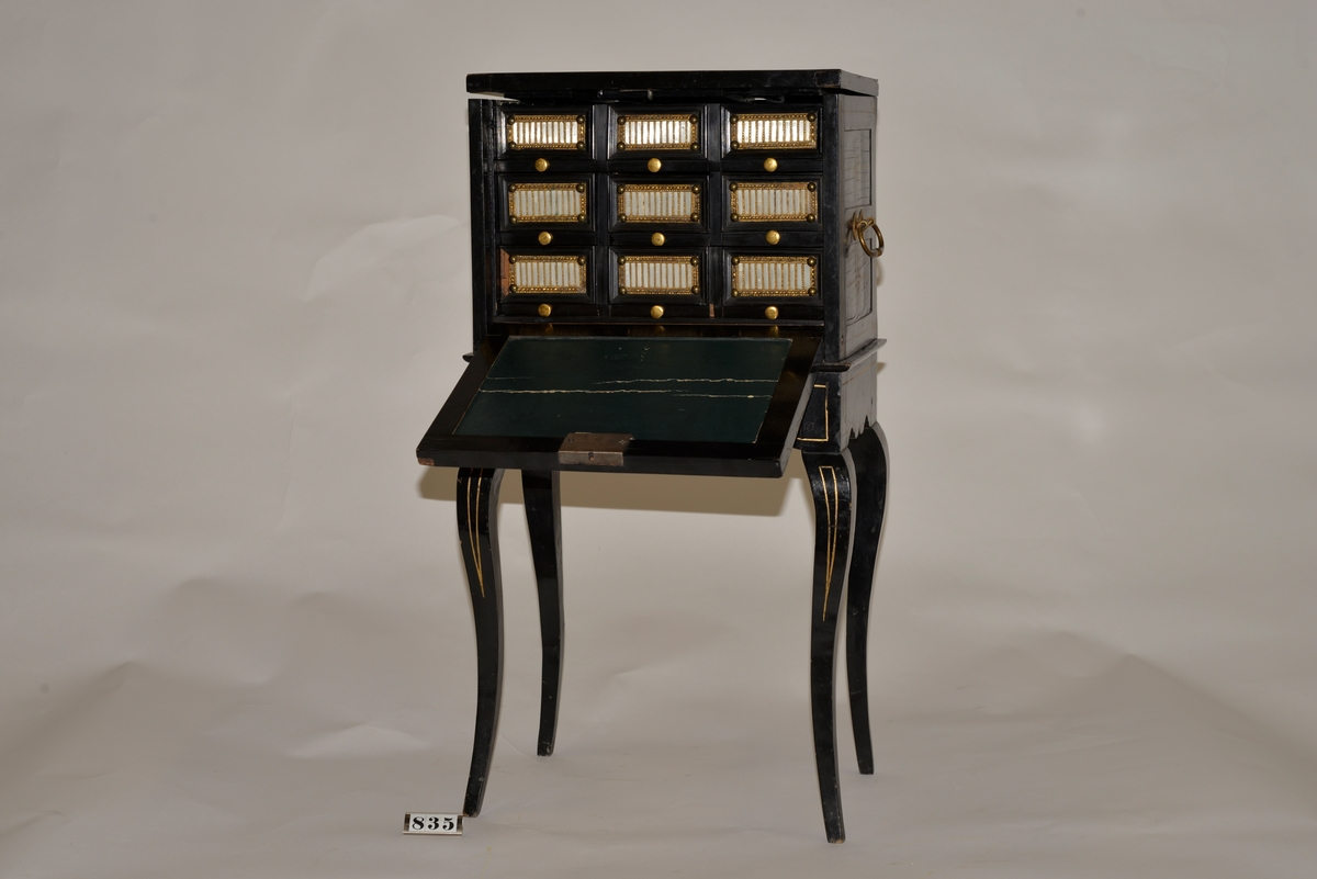Mindre svartlackerat skåp på fyra ben och med sex lådor.