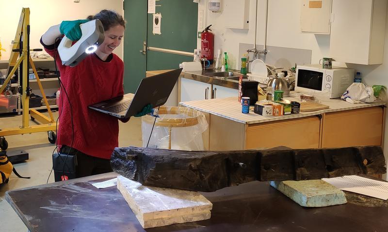 Arkeolog holder en skanner i høyre hånd og en bærbar datamaskin i venstre hånd, og peker skanneren mot en båtdel som ligger på et bord. (Foto/Photo)