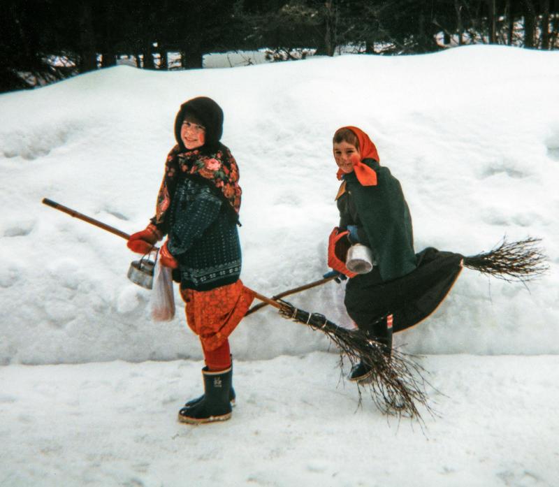 To jenter utkledd som gamle kjerringer med skaut på hodet står ved en snøkant med hver sin sopelime mellom bena, klare til å fly av gårde som påskehekser.