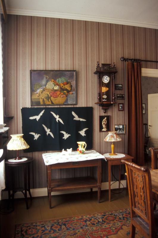 Spisestua i «Vaskekonen Gunda Eriksens hjem — 1950» har originale papirtapeter fra l930-tallet. På tregulvet ligger et last linoleumsteppe av typen Congoleum. Det dekker mye av gulvet og ligner på avstand til forveksling et persisk teppe. Linoleumsbelegg og -tepper med slike mønstre var høyeste mote fra slutten av 1800-tallet og ble mange steder liggende helt fram til 1950-tallet, ettersom de var så slitesterke. (Foto/Photo)