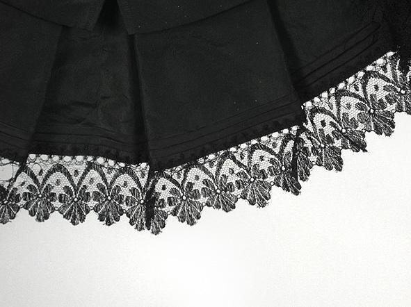 Brudklänning av svart vattrat siden, bestående av liv, kjol samt skärp med skört.  1. Livet: knäppning fram, sex tränsade knapphål och sex överklädda knappar (varav en fattas). Rund halsringning (halskrås eller krage bortsprättad). Trekvartslång passpoalinsydd ärm, draperad, påsydda snedslåar, volang nedtill, svart spets i kanten. Vit spets i nederkanten. Inprovning på framstycket, livsömmar bak. 2 st hakar mitt på bakstycket för att knäppa fast kjolen. Foder av beige linnelärft. Mått. Rygglängd 420 mm. Ärmlängd 490 mm. Midjevidd 650 mm.   2. Kjolen: Sju våder, fodrad med brun gasväv. Påsydd linning i midjan mot stripade veck i sidorna. I nederkant skoning av grönt kyprat ylle samt 22,5 cm brett slitband i kanten. Hänghällor på överkantens insidor. Mått: Längd fram 1000 mm. Längd bak 1150 mm. Linning 40 mm.  3. Skärp: spetskantat skört, veck mitt bak, klädda knappar samt stående rosett.  Mått: Skörtet bak 220 mm. Spets 50 mm.