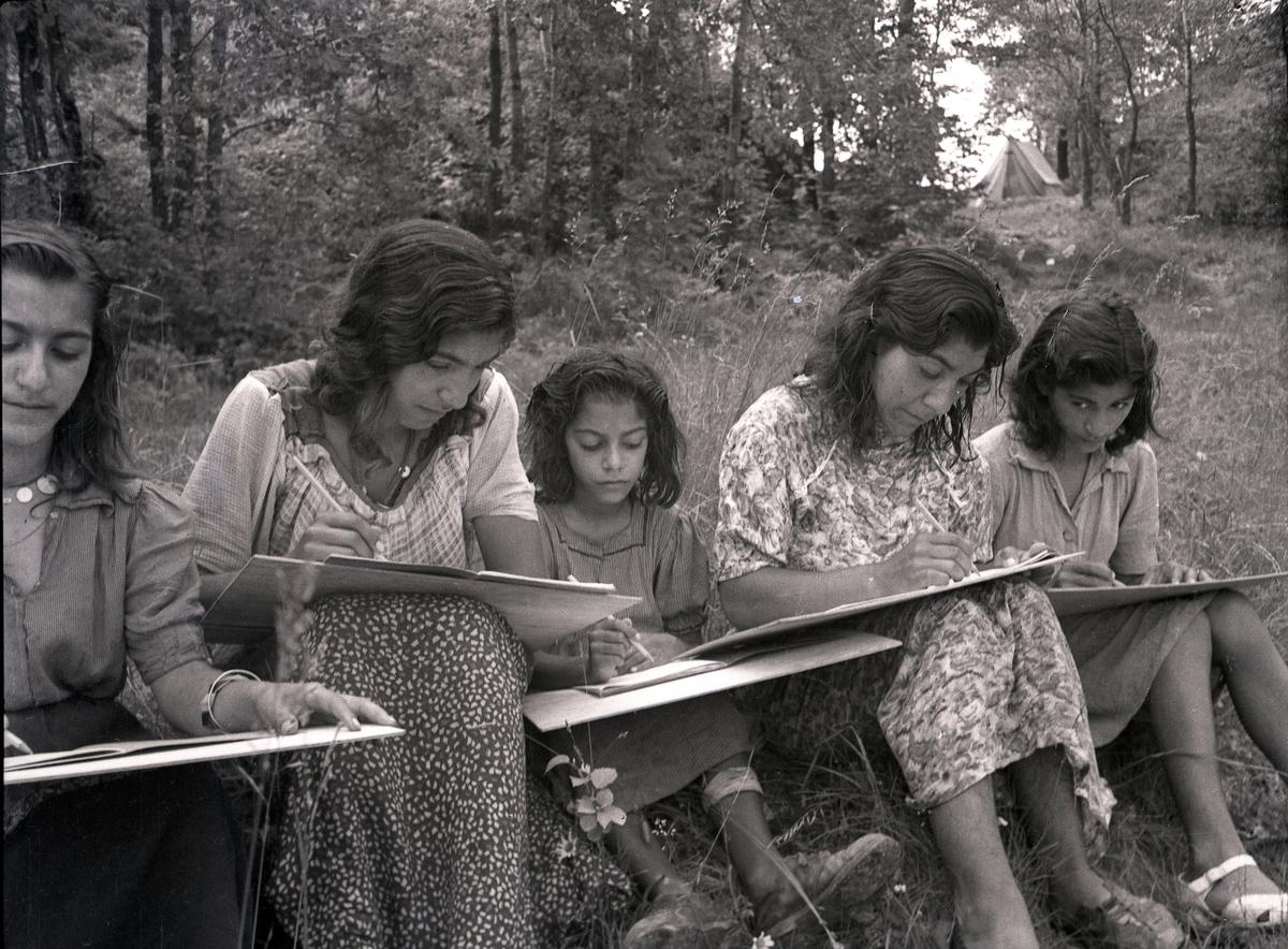 """På rad i gräset sitter unga kvinnor och flickor med skrivplattor. I bakgrunden skymtar tält. Bilden är troligtvis tagen i samband med någon av de kurser som arrangerades för romer i mitten av 1900-talet, som kompensation för förlorad skolgång. Stiftelsen Svensk Zigenarmission, grundad 1945, drev sommarskola för romska elever under hela 1940- och 1950-talen. Eleverna var mellan 6 och 60 år och satsningen blev mycket medialt uppmärksammad. Zigenarmissionen var dock kritiserad, både av romer och icke-romer, då man ansåg att romska barn skulle få samma möjligheter att gå i skola som andra svenska barn.  Efter en tid med olika former av försöksverksamhet föreslog den s.k. """"Zigenarutredningen"""" (1954), att romer skulle gå i vanliga skolor. Frågan om undervisningens organisering fick de enskilda skolorna att hantera på egen hand men från och med juni 1960 fanns möjlighet för kommuner att rekvirera bidrag från staten för speciell undervisning av romska barn. Undervisning för romer arrangerades även av bland annat folkhögskolor och studieförbund. Först efter att alla romer fick bli bofasta på sextiotalet, fick samtliga svenska romer tillgång till skolundervisning."""