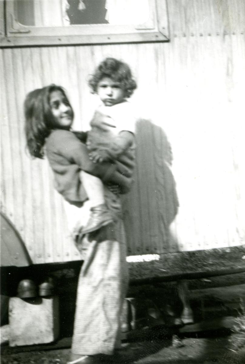 En flicka står framför en bostadsvagn med ett mindre barn i famnen. Bilder är tagen framför en bostadsvagn i Göteborg. I Göteborg finns flera platser runt om i staden med koppling till svenskromsk nittonhundratalshistoria. Lägerplatserna förlades ofta i vad som då var stadens ytterområden eller andra icke-planlagda områden. Romska lägerplatser har funnits bland annat i Fredriksdal (1920-tal), Kvillebäcksområdet (1920-talet) och i Bergslagsparken (1950-tal). Den här bilden är troligen tagen i närheten av Göteborgs centralstation, då man på relaterade bilder kan se godsvagnar i bakggrunden. År 1944 gör SVT ett reportage från ett romskt läger vid Kruthusgatan, möjligen är bilden tagen där eller i närheten.