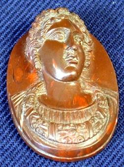 På oval platta som bakgrund är utskuren i relief en byst föreställande en man med utseende av en romersk kejsare. På huvudet sitter en krans och runt halsen hänger en smyckeskrage.