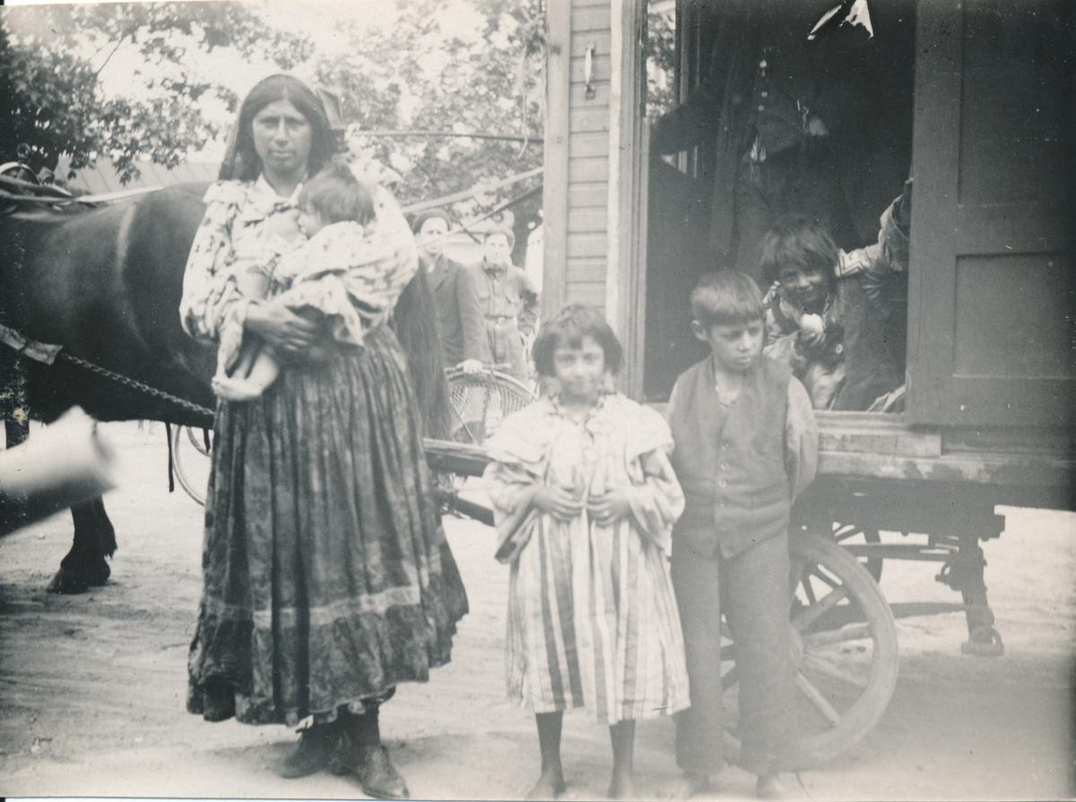 En kvinna ser in i kameran samtidigt som hon ammar ett spädbarn. Bredvid henne på marken står ytterligare två barn och bakom dem syns en hästförspänd bostadsvagn. Boendestandarden för svenska romer var under 1900-talets första hälft mycket varierande. Familjer som hade det bättre ställt kunde äga flera tält, medan fattigare familjer enbart hade ett tält. Man sov då där marken var minst lerig. På 1940-talet, efter krigsslutet, förbättrades levnadsstandarden och flera svensk-romska familjer specialbeställde bostadsvagnar. Att inte behöva sova på marken utgjorde en avsevärd förbättring av livskvaliteten. Eftersom vagnarna specialbeställdes kunde beställaren vara med och påverka vagnens utformning. Ofta fanns sovgemaket längst in, varpå vardagsrummet följde och köket låg längst ut. Denna utformning kunde dock skilja sig åt mellan olika vagnar. Generellt var vagnarna dåligt isolerade och kalla att bo i. Först på 1960-talet tilläts svenska romer att bli bofasta.