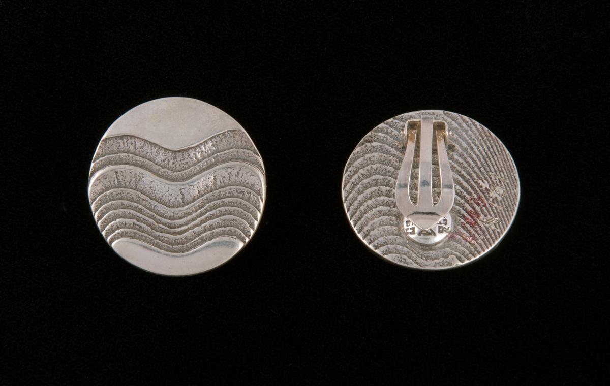 Støpt, blankpolerte øreklips av en rund , flat sølvplate med støpt dekor. Klipsfeste skjult på baksiden. Dekor av horisontale stiliserte bølger i lavt relieff.