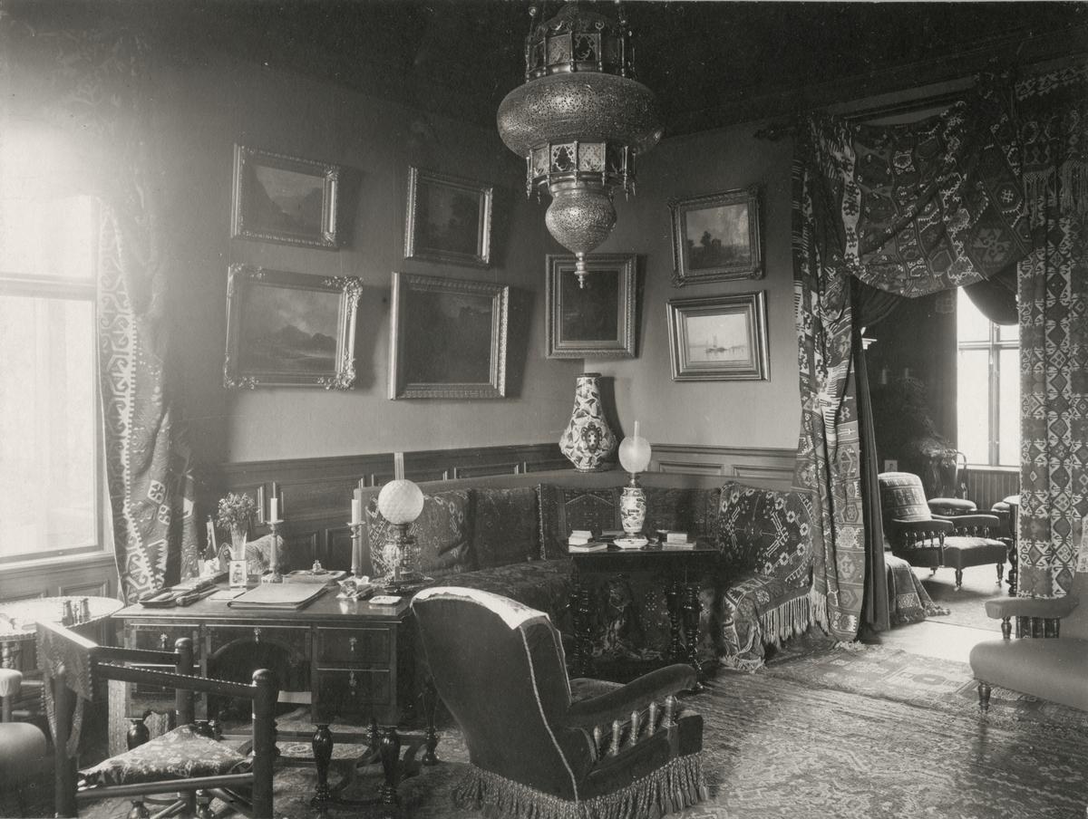 Interiör från Villa Rettig. Litet damskrivbord med munkstol. Ottoman med matchande kraftiga draperier. I taket hänger en orientalisk lampa.