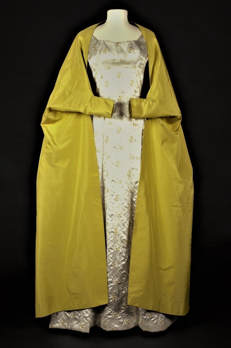 """Sydd av dobbelt lag, ripsartet silke, dvs. fôret med samme materiale. Meget utskrådd fasong, der det utskrådde ryggstykket går ut fra et rundet bærestykke i nakken. Mens ryggstykket er skåret iett, er bærestykket samlet i en søm midt bak og ellers skåret iett med skuldre, ermer og de vide forstykkene. I albuhøyde, er forstykkenes fremre kant """"heftet opp"""" og sydd sammen til et trangt, lite erme for underarmene. På den måten blir plagget en mellomting mellom en cape og en kåpe, og plagget en del kortere foran enn bak."""