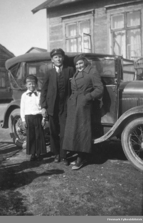 En familie fotografert ved siden en bil og hus. Stedet er mest sannsynligvis Salttjern.