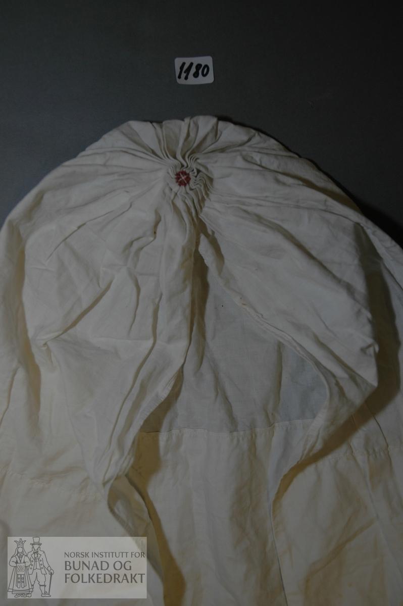 Kambrik. Rektangulært stykke. Framkanten er i dobbelt stoff, lengd 40,5 cm. Hetta er teke saman midt bak med djupe striperynker og sydd saman med mørk brun (truleg)silke, raudfiolett kamgarn og kvitt bomullsgarn. På vranga er rynkene teke saman med bomullsgarnet. Oppbretten er vrangsydd. Smal fald vidare til rynkinga. Dei to falda sidene er tekne saman 3,5 cm frå samantrekkinga og utover. Åtte cm frå framkanten skrår breidda inn med 4 cm. Hand- og maskinsaum.  Breidd framkant:  61 cm. Heil breidd:      65 cm. Høgd hette:     63,5 cm.