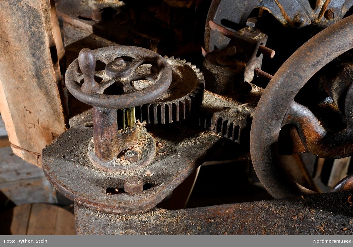 BESKR: Rektangulær ramme av jern som står på 4 par bein, ett par på hver side. Alle beinpar skrår utover mot gulvet, 2 par buer utover, 2 par skrår rett utover. 2 aksler er festet oppå rammen, midt på parallellt med siden. Disse ligger i plan med hverandre, horisontalt og vertikalt, men er uten forbindelse når et bunnemne ikke er fastspent i maskinen. Hver aksel roterer i 2 oljelagre sveiset på rammen. Den ene akselen er gjenget og kan via et ratt forflyttes horisontalt mot den andre akselen. Den andre akselen er drivakselen. Mellom lagrene er 2 reimhjul festet på akselen, et frihjul og et drivhjul. På den indre ende av hver aksel er festet en skive. Skiva på drivakselen er fast, akselen og skiva dreier i ett. Små pigger på innsiden av hver skive gir ekstra godt feste på bunnemnene. I skruakselen roterer skiva fritt på akselenden. På den ene siden av rammen er festet 2 tannhjulutvekslinger, tannhjul og tannstang. På hver tannstang er festet 2 skjærekniver, en rett og en buet. 2 bord fra rammen til taket beskytter operatøren fra trebitene som skjæres løs. 2 oljelagre på de utsvungne bein kan være fra en tråmekanisme. Ifølge Egil Brudeseth f.1892, var bunnmaskinen i Christoffersen-brygga (Wold-brygga) opprinnelig en tråmaskin. Reim fra drivhjulet til drivakselen under taket driver maskinen.  BRUK: Skjære bunnene runde og skrå kanten samtidig.