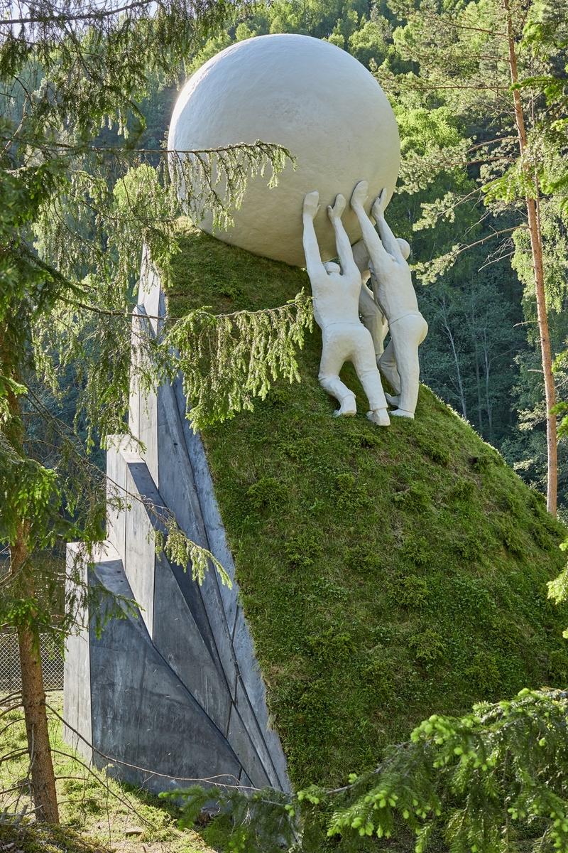 Installasjonen består av et konstruert betongfjell som på baksiden har fjellhyller. Fremsiden er en bratt bakke dekket med planter og busker. Tre menn støtter opp en ball som ligger helt øverst i bakken, rett før stupkanten på andre siden.