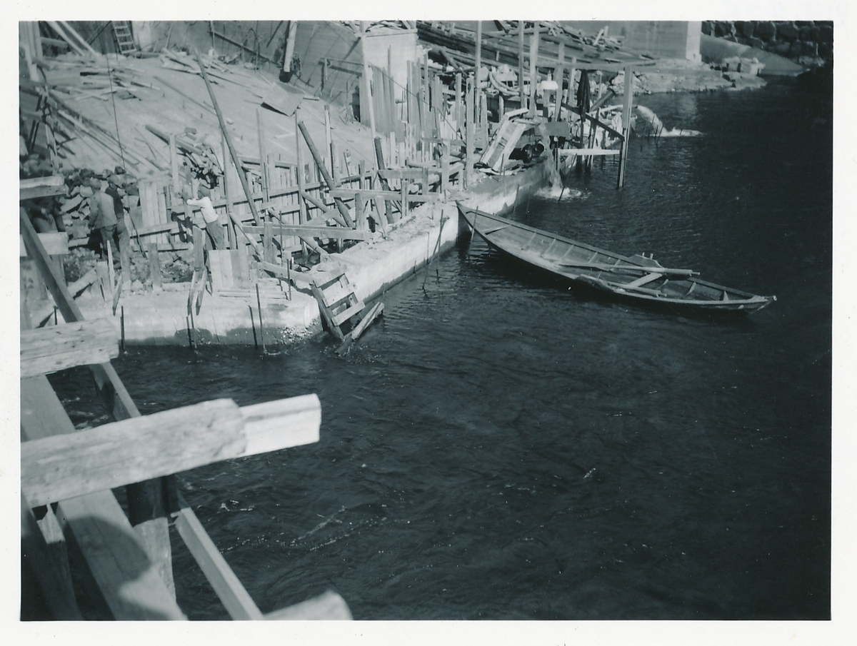 Anleggsarbeid med dammen ved kraftverket på Kistefoss. Robåt med ett toftepar ligger i vannet.