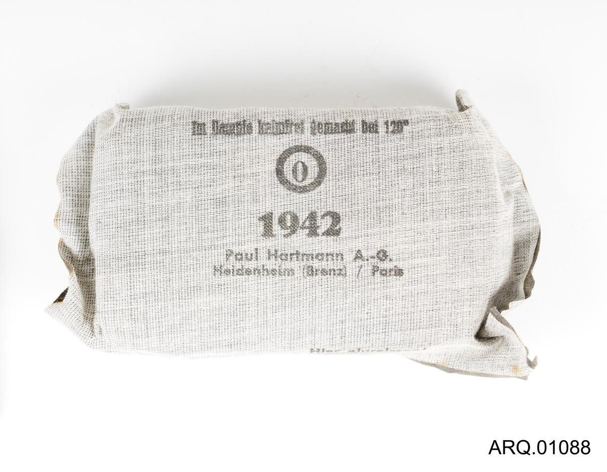 Gasbind i original-innpakning. Innpakning er i en lysegrå, slags seilduk-tekstil med bruksanvisning på.