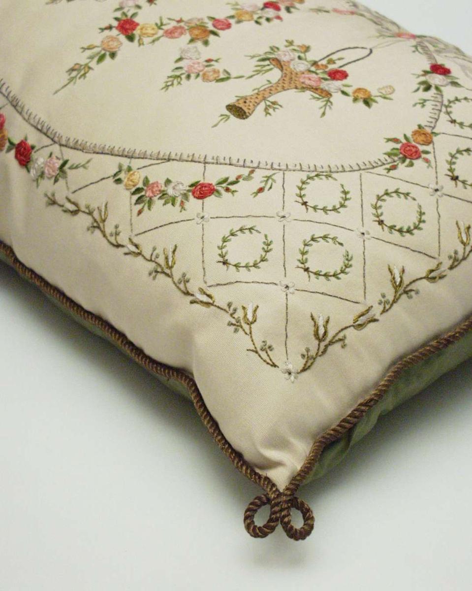 På beige silkeripsbunn broderi med silkesting, kjedesting, plattsøm, leggsøm og knuter. Motiv: ovalt midtfelt 40x26 cm markert med oval ramme. På øverste rammekant bølgete bånd med sløyfe midt på. Herfra henger en blomsterkrans. På hver side en kurv med blomster. Utenfor det ovale feltet mot en rektangulær ramme 54x31 cm, avgrenset av en svakt bølgete blomsterknupp- og greinranke er det et rutenett av leggsøm med metalltråd. I hver hel rute en grønn bladkrans (laurbærkrans) av kjedesting. I nederkant av ovalformen tre blomsterguirlandere. Baksiden av grønt silkestoff. I kantene påsydd en metallsnor, to løkker i hvert hjørne. Rester av tråder, slitasje og fargen på metallet tilsier at snora er flyttet over fra den gamle puten.