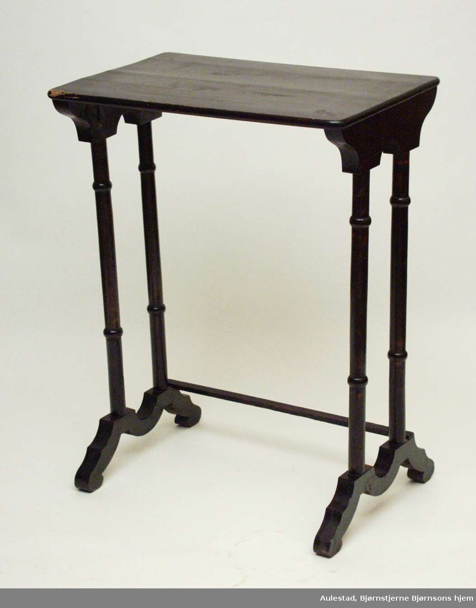 Settbord i bjørk beiset og lakkert mørk brunt. Fire søyler går på kortsidene ned i bølgebuende fotstykker. De er forbundet med en firkantet sprosse. Bordplaten er laget i gran.
