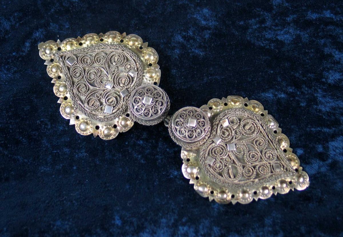 Todelt hjerteformet hekte i sølv med filigransdekor. Forgylt gjennombrutt kant.