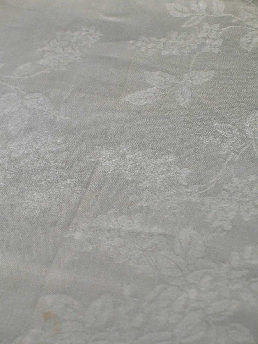 Hvit jacquardvevet duk i lindamask. Den har blomstermotiv og er omsydd. Ca 1,5 cm maskinfald på alle sider. Nederst en 17 cm bred umønstret kant, dernest en blomsterbord, rapportlengde 20 cm. Videre oppover er blomsterrankene åpne og grenete. En rapport: høyde ca 30 cm.