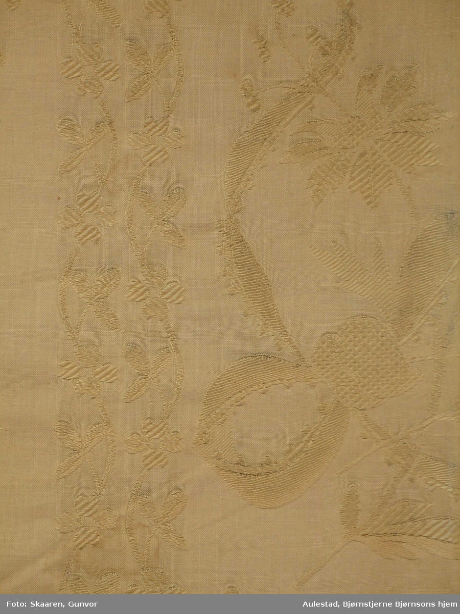 Jarene er innbrettet, 7,5 cm i hver side, sydd med maskin både i brettekant og ved jarene. 5 cm brett nederst, sydd ned med maskin. Maskinsøm også i brettekant, samt trådrester etter opplukking. I øverste kant rustmerker og hull etter feste til rullen. Mønster: skiftevis brede og smale vertikale blomsterranker med sløyfebånd. En rapport: 23x 44 cm.