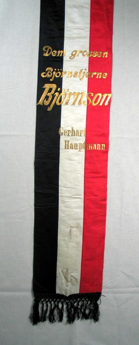 Begravelsessløyfe i hvit, rød og svart silke med svarte frynser og tekst i gull.