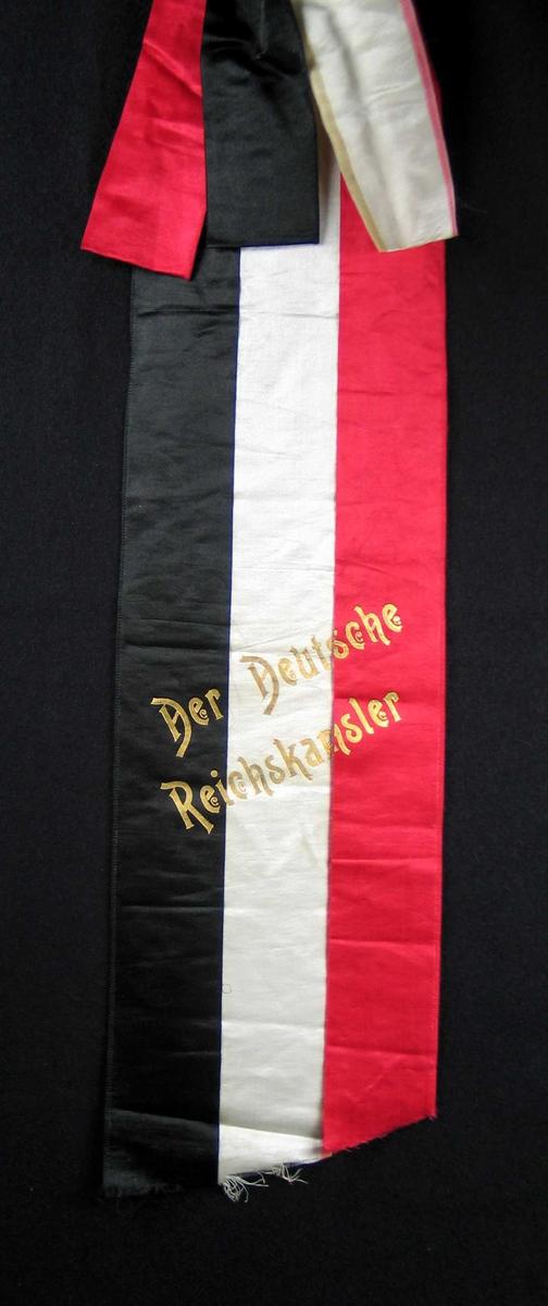 Begravelsessløyfe i rød, hvit og svart silke med tekst i gull.