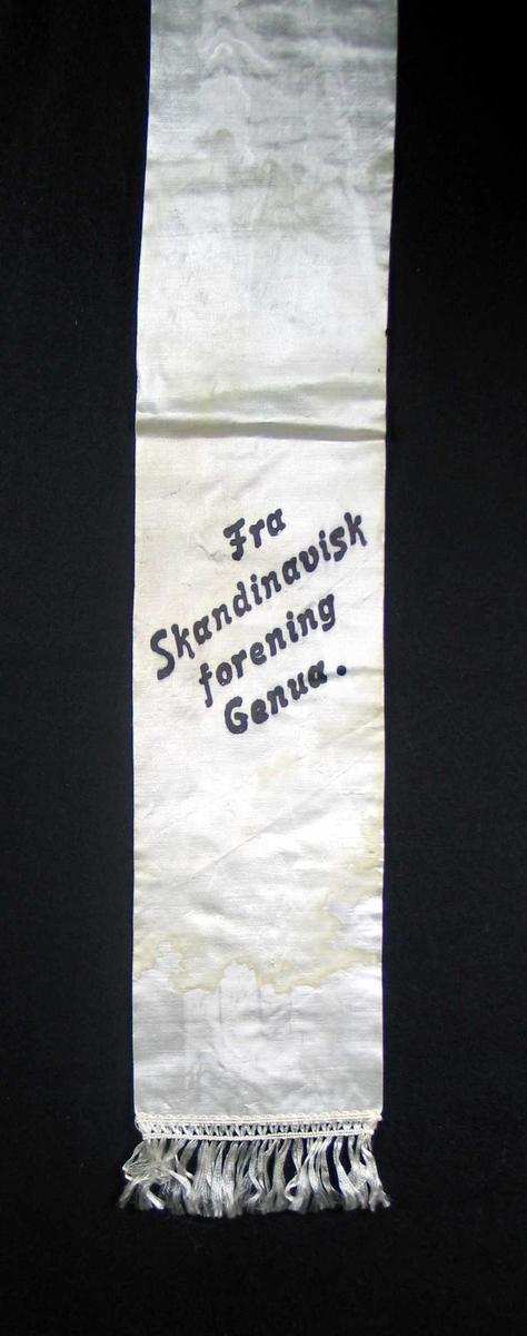 Begravelsessløyfe i hvit silke med svart tekst. Frynser.