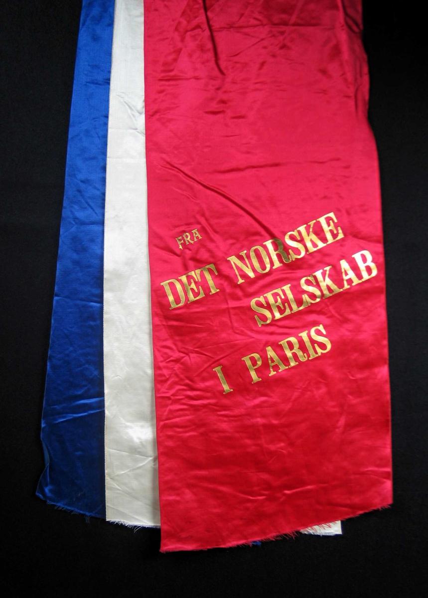 Begravelsessløyfe i rød, blå og hvit silke med tekst i gull.