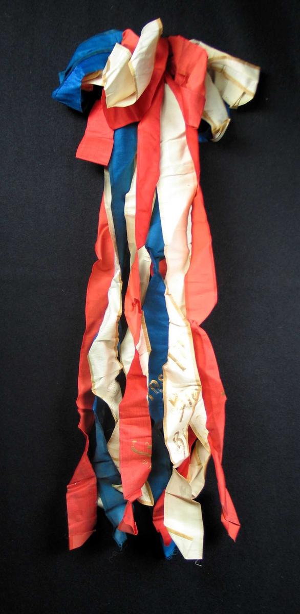 Begravelsessløyfe i rød, hvit og blå silke.