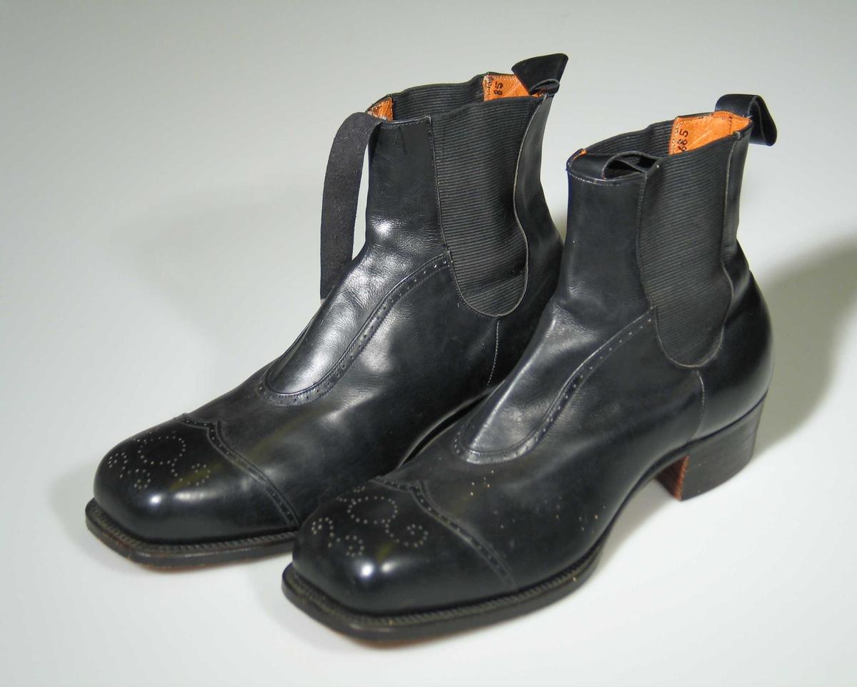 Et par svarte skinnstøvler med strikk i sidene og hempe foran og bak. Dekorert med hullmønster.