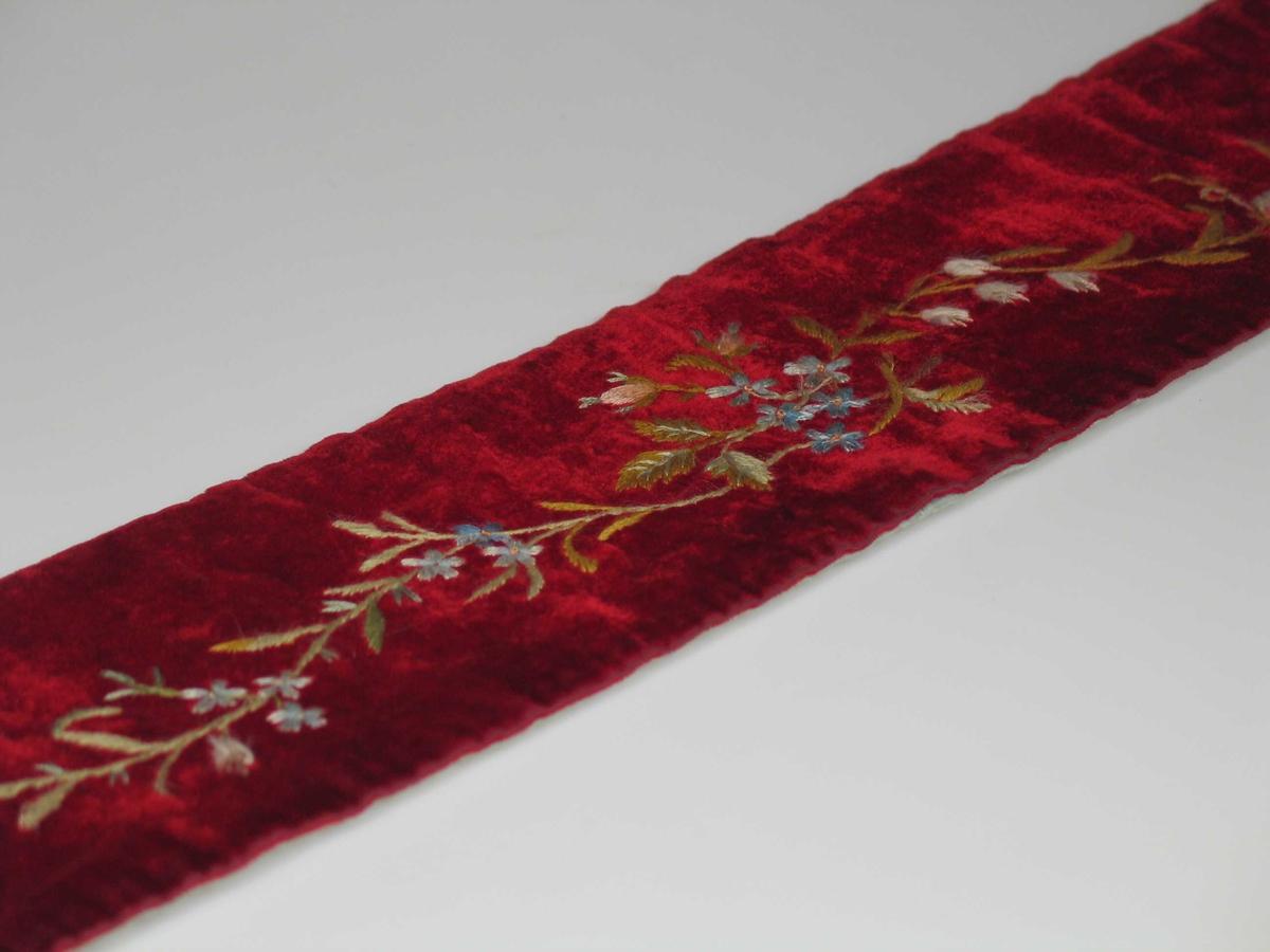 Løper brodert på rød fløyel. Vattert og fôret med lys blå silke. Flygelløper/tangentbeskytter. Teknikk: Silkesting, plattsøm og knuter i greiner, blad, blomster i tynt rankemønster langsetter løperen.