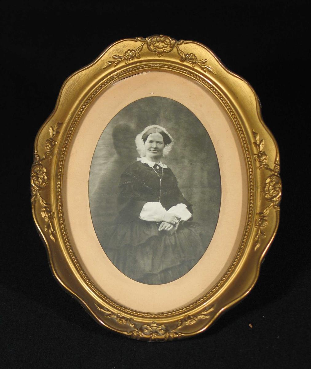 Sittende kvinne med mørk kjole, blondekrage og lyst hodeplagg.