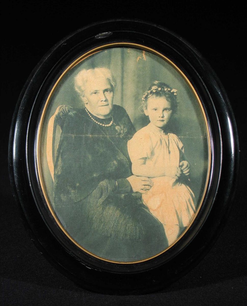 Fotografi i svart oval ramme med gullkant innerst.